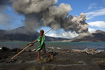 Munganau Buej, 9 years old, loves to play on the beach. Every day the young boy swim in the salt water to rinse off the ash, Tavurvur Volcano, Rabaul, East New Britain, Papua New Guinea, Melanesia- Pacific