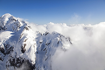 Helicopter flight over snowy mountains with low cloud, Bryneira Range, Southern Alps, South Island, New Zealand