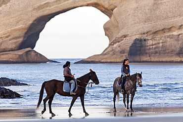 Horse ride along Wharariki beach near Farewell Spit, Archway Islands in the background, South Island, New Zealand