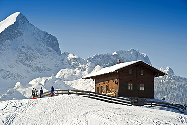 People sledging at Eckbauer, Alpspitze and Zugspitze in the background, Garmisch-Partenkirchen, Bavaria, Germany