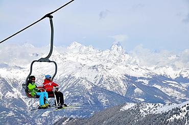 Two people in a ski lift, Pila ski resort, Aosta with Matterhorn, Aosta Valley, Italy