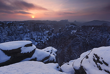 Sunset above the Saxon Switzerland national park with a wide view from Carolafelsen above the heavily snow covered landscape, Saxony, Germany