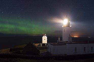 Impressive northern lights, auroras above Dunnet Head lighthouse on the northeast coast of Scotland, United Kingdom