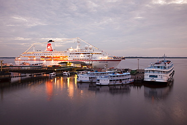 Cruise ship MS Deutschland (Reederei Peter Deilmann) and Amazon river boats at dusk, Manaus, Amazonas, Brazil