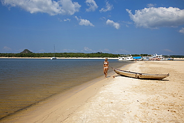 Woman strolling along the beach on a side arm of the Amazon river with Amazon river boats in the distance, Alter do Chao, Para, Brazil