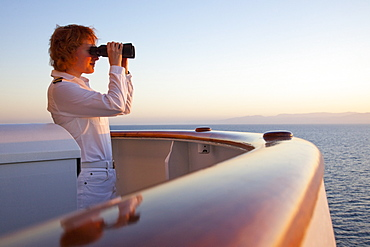 Safety Officer Claudia Kempkes with binoculars on the bridge nook of cruise ship MS Deutschland (Reederei Peter Deilmann) at sunset, Gulf of California, near Mexico