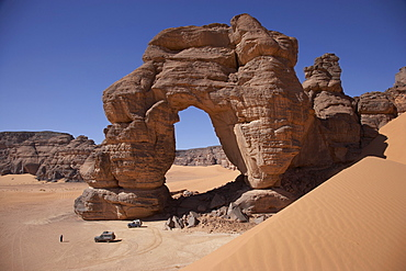 Off-road vehicles near a natural arch, Tadrart Acacus, Ghat District, Lybia
