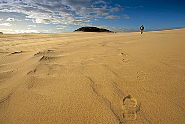 Person walking along the Thurra sand dunes, Croajingolong National Park, Victoria, Australia