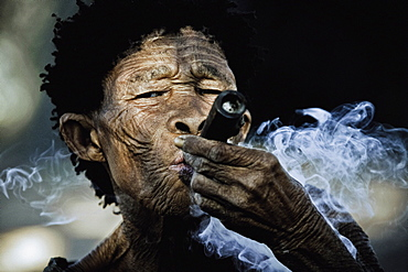 Old woman from the San tribe smoking Dagga, Otjozondjupa region, Namibia, Africa