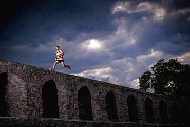 Man running along castle wall, Linz, Upper Austria, Austria