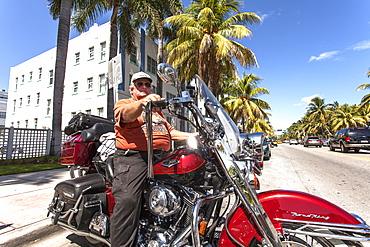 Senior adult on a Harley Davidson motorcycle on Collins Avenue, Art Deco District, South Beach, Miami, Florida, USA