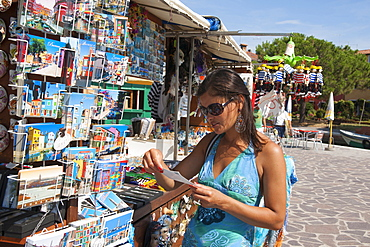 Young woman buying postcards, Burano, Venice, Venezia, Italy, Europe