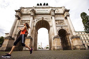Female jogger passing Siegestor (vitory gate), Munich, Bavaria, Germany