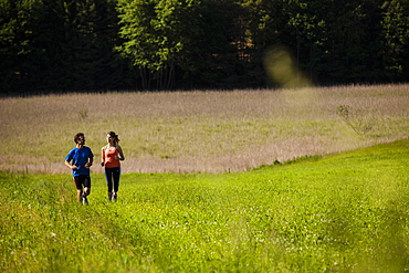 Two joggers running over a meadow, Upper Bavaria, Germany