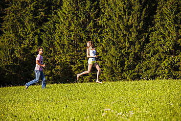 Couple running over a meadow, Upper Bavaria, Germany