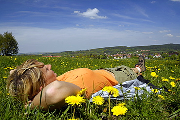 Woman lying in a meadow, hiking tour near Tabarz, near Eisenach, Thuringia, Germany