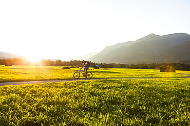 Mountain biker passing meadow with hay barns, Grainau, Bavaria, Germany