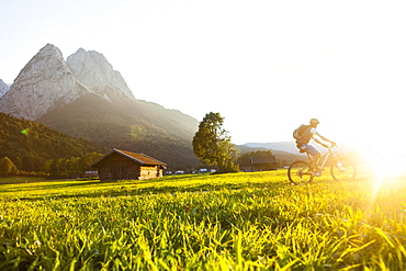 Mountain biker passing meadow with hay barns, Grainau, Bavaria, Germany