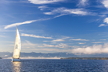 Sailing boat on Lake Starnberg, the Alps in background, Bavaria, Germany