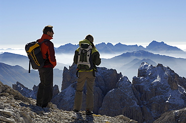 Couple admiring the view, hiking in the mountains, Val di Fassa, Rosengarten, Dolomites, Trento, South Tyrol, Italy