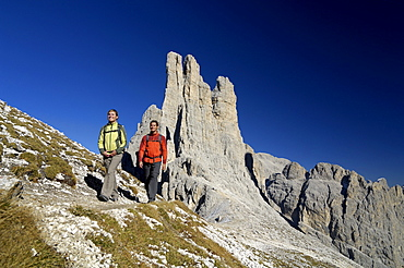 Couple hiking in the mountains, Vajolet towers in the background, Rosengarten, Dolomites, Trento, South Tyrol, Italy