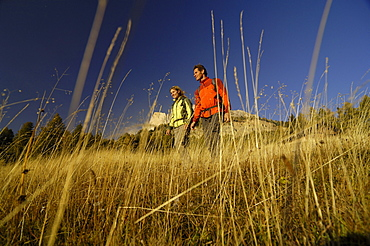 Couple hiking in the mountains, Near Welschnofen, Rosengarten, Dolomites, Trento, South Tyrol, Italy