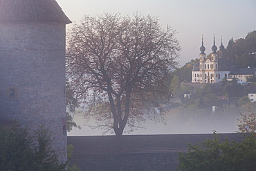 Marienberg fortress surounded by fog and Capuchin cloister Kaeppele, Wuerzburg, Bavaria, Germany