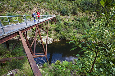 Couple standing on an old railway bridge over the Thomson River, Walhalla, Victoria, Australia