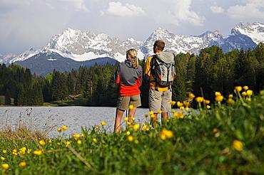 Couple on the lake shore admiring the view, Lake Gerold, near Klais, Upper Bavaria, Bavaria, Germany, Europe