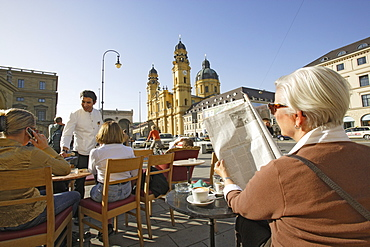 A woman reading the newspaper on the terrace of Cafe Tambosi, view at Theatinerkirche, Munich, Bavaria, Germany