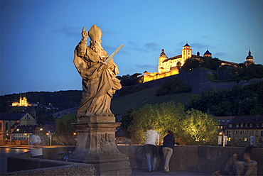 Statue on the old Main Bridge with view of Marienberg fortress at night, Wuerzburg, Franconia, Bavaria, Germany