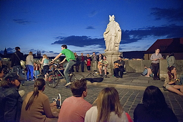 Evening mood with street artists and young people on the old Main bridge, Wuerzburg, Franconia, Bavaria, Germany