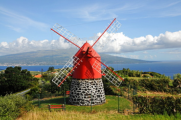 Windmill over Praia do Almoxarife with Pico Vulcano in the background, Island of Faial, Azores, Portugal