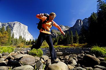 Woman wearing rucksack jumping over stones at brookside, Yosemite National Park, California, North America, America