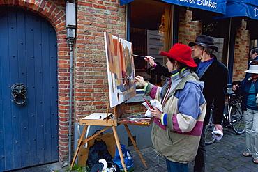Painters painting a street scene, Bruges (Brugge), West Flanders, Belgium