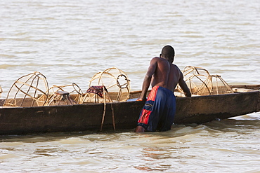 Fisherman and his nets on a boat in Lake Débo, formed by the seasonal flooding of the Niger River, Mali