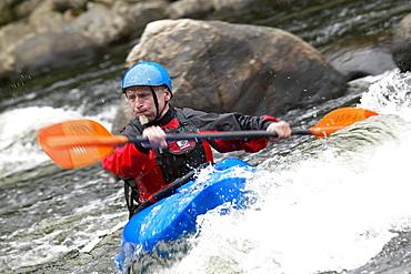 Man Kayaking in White Water.