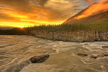 Orange sunset on Sluice Box Rapids above Virginia Falls, Nahanni National Park, Northwest Territories