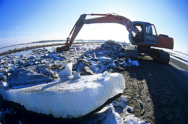 A Front Shovel Excavator unblocking Ice buildup which has caused Flooding of Agricultural Land during Spring Runoff, near Dugald, Manitoba