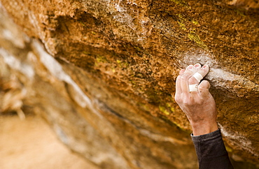 Mans Hand Clinging to Rock while Climbing