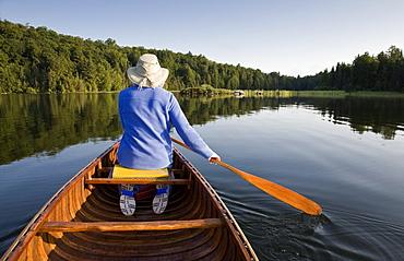 Woman paddling canoe on Smoke Lake, Algonquin Park, Ontario