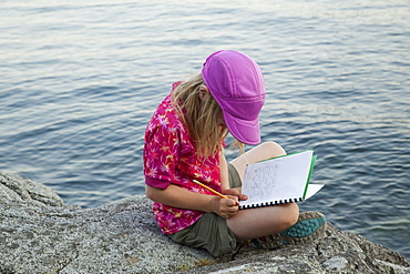 Grade 3 girl taking notes during a school outing, Keats Island, British Columbia