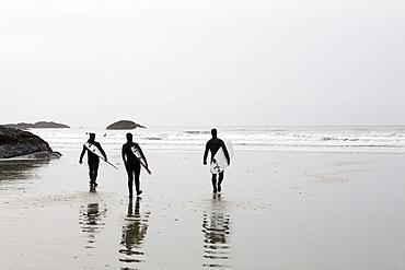 Three Surfers Walk on Beach Toward the Surf, Tofino, British Columbia