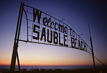 Sign over entrance to beach at sunset, Sauble Beach, Ontario, Canada