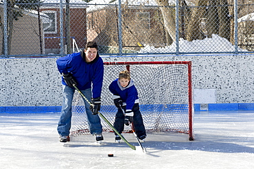 Father and son hockey players on an outdoor rink, Toronto, Ontario