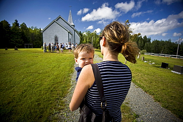 Mother carrying her young boy towards a small Catholic church in Merland, Antigonish County, Nova Scotia