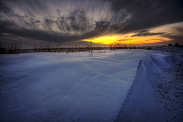 Sunrise over snow drifts and wheat stubble on the Alberta prairies