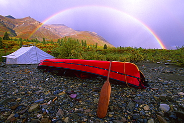 Canoe and Tent at a Campsite with a Rainbow and the MacKenzie Mountains in the Background in Autumn, Snake River, Whitehorse, Yukon