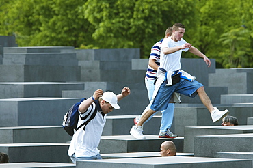 Boys playing on the stelae of the Memorial to the Murdered Jews of Europe, Berlin, Germany