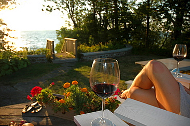 Woman's Legs on Deck Chair with Wine Glasses, Lake Simcoe, Ontario
